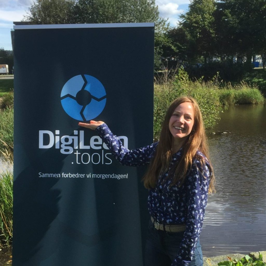 Caucasian woman presenting DigiLEAN.tools in front of roll-up poster outside next to water pond