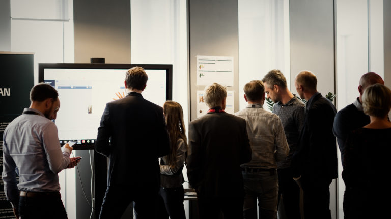 Groups of people in front of a DigiLEAN presentation on a touch screen