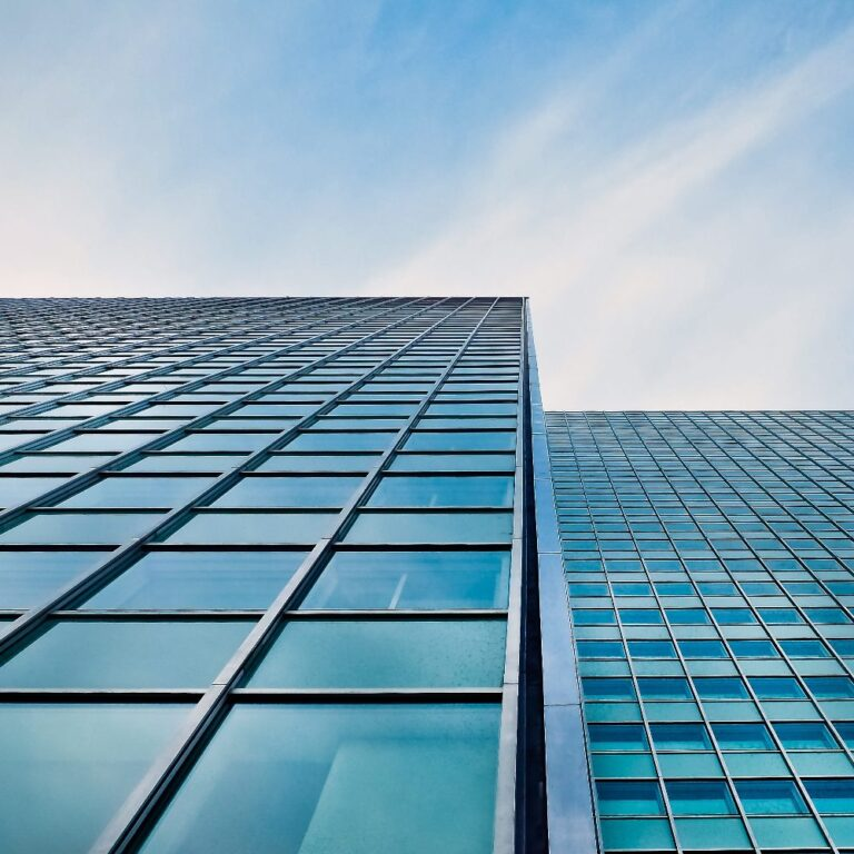 Tall building perspective. Glass and blue skies with light cloud cover