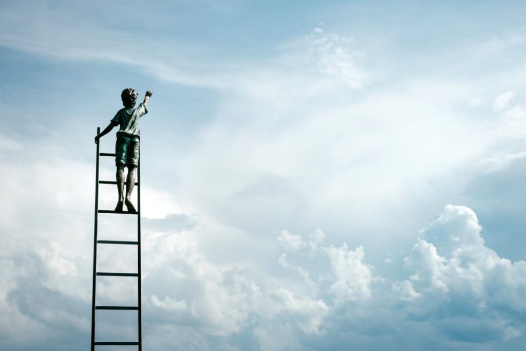 A boy on the top of a ladder going up towards the sky.