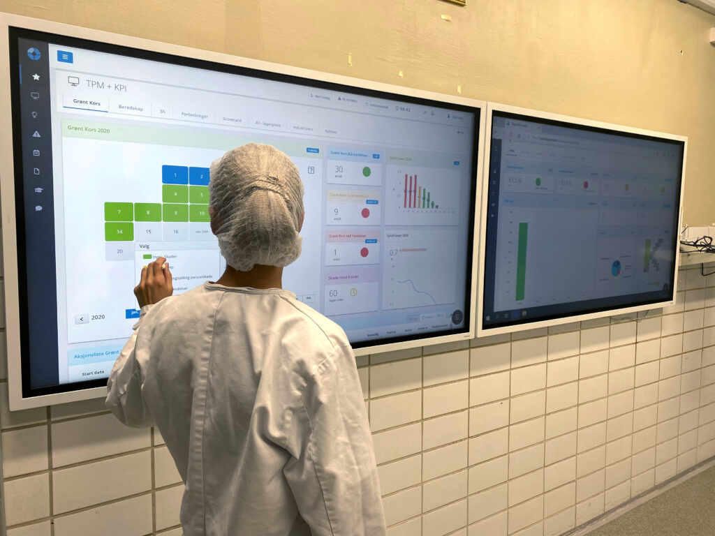 A woman in white protective cloths in front of two touch monitors with TPM boards created in DigiLEAN, used by Kavli, a food production company.