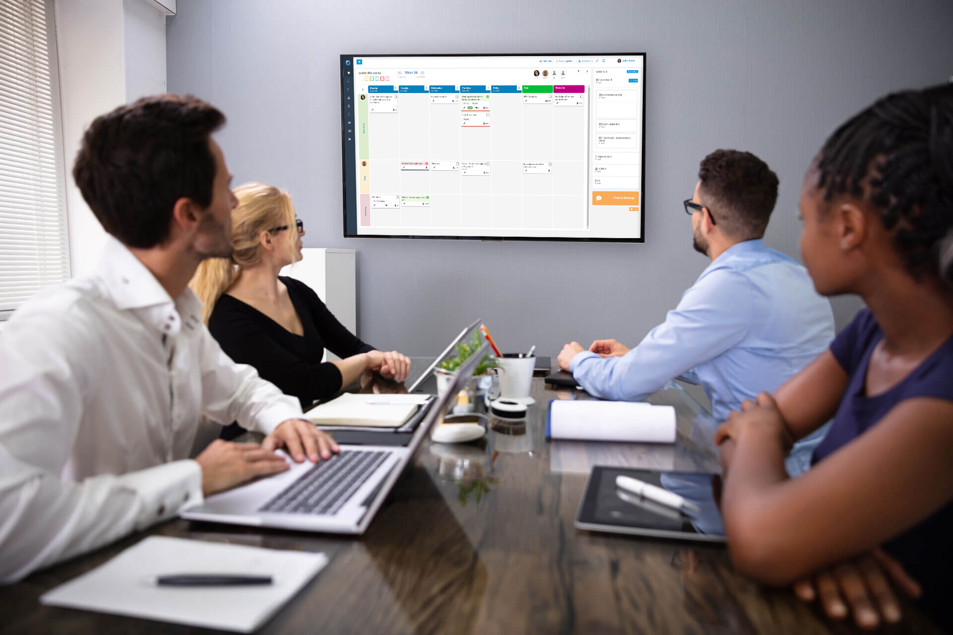 A four member team gathered in a meeting room with DigiLEAN on a wall monitor