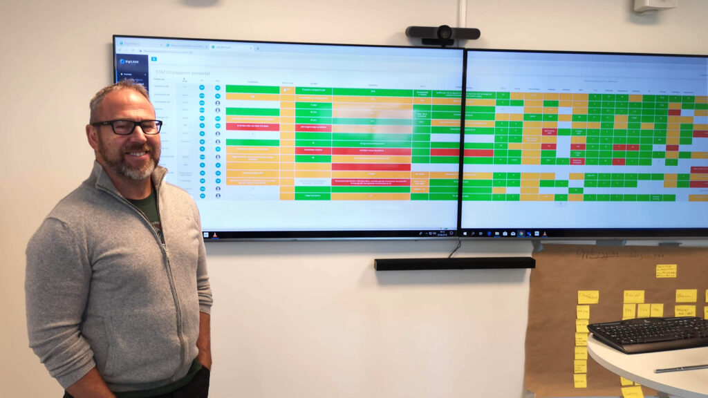 Terje Nøttveit standing in front of dual screen setup with DigiLEAN showing project management board